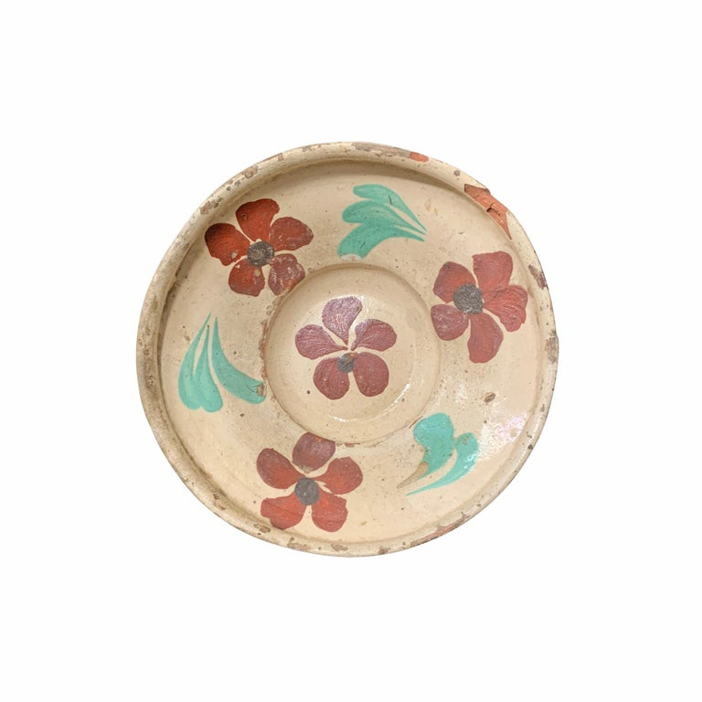 A fantastic and rare set of twelve 19th century Hungarian folk ceramic bowls, each slip glaze painted with unique floral patterns in various colors. Each bowl has the original string on the back which was used to hang the bowl on a wall in the