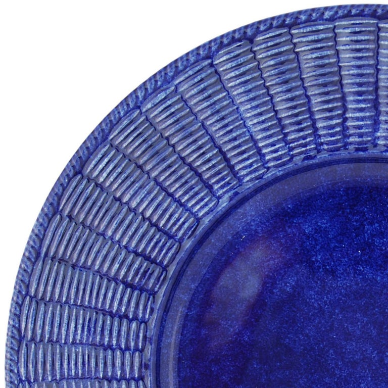 This is a set of twelve large plates conceived as placeholders, to be left as base as courses change, finished in a rich shade of blue with a sponge effect. The pieces are characterized by Este Ceramiche's signature wicker border, flawlessly created