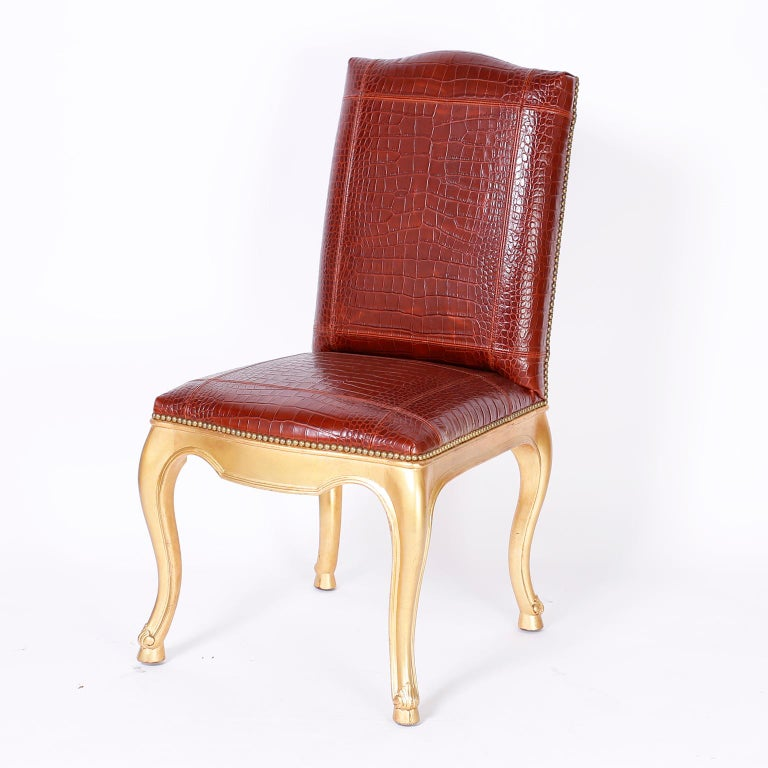 Stand out set of twelve dining chairs with oxblood faux alligator tooled leather upholstery bordered in brass tacks over gold cabriole legs with acanthus leaves and hoof feet. Signed Ralph Lauren.