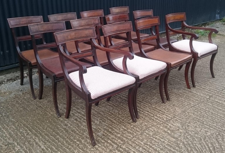 Very fine and well drawn set of twelve early 19th century Regency mahogany antique dining chairs. This set of chairs are larger than normal for the period with good deep seats and a generous splay to the legs. Sabre leg chairs are especially elegant