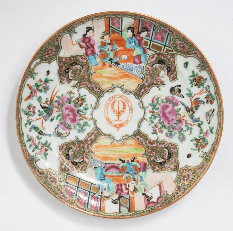 A set of 12 porcelain plates, Famille vert decoration Depicting various shaped cartouches of; figures in interiors, flora and birds. Each plate centred by a coat of arms. Chinese, circa 1900 Measures: 24.5 cm diameter x 2 cm high.