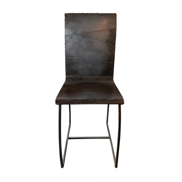 A fantastic set of twelve French artist-made Brutalist style dining chairs constructed of pieced welded steel seats on simple thin bent steel legs. Each pieced pattern is unique.