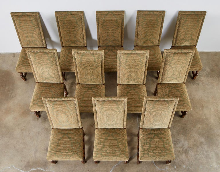 Bespoke set of twelve upholstered dining chairs made in the French Louis XIV taste also known as Os de Mouton chairs. The matching chairs feature a textured fabric in moss green and camel hair color with a subtle foliate design. The fabric is