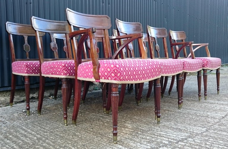 Set of twelve George III period mahogany antique dining chairs, ten singles and two armchairs, standing on elegant turned legs with good close reeded decoration and unusual brass caps. These chairs have been re-railed using good quality close