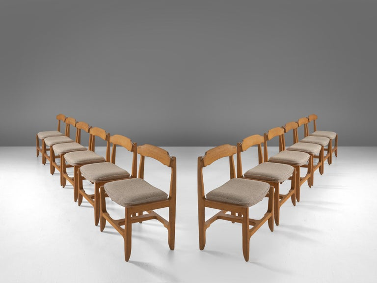 Guillerme et Chambron, set of 12 dining chairs, solid oak, grey upholstery, France, 1960s.  These distinctive chair in beautifully patinated oak is by the French designer duo Jacques Chambron (1914-2001) and Robert Guillerme, (1913-1990). These