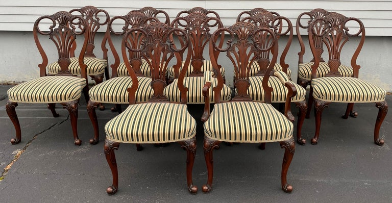 A beautiful set of twelve Italian custom mahogany Queen Anne style dining chairs, including 11 side chairs and one arm chair, with pierce carved back splats, cabriole legs terminating in scrolled ball feet, and finished with bold striped upholstery.
