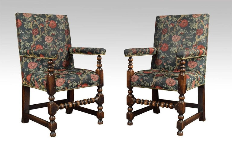 Set of Jacobean style oak framed dining chairs with fully upholstered seat, back and arms all raised up on turned legs and stretchers.