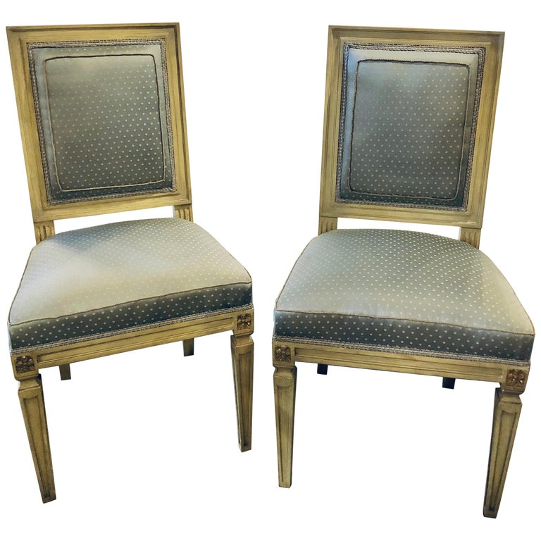 Set of twelve Jansen style paint decorated and Gilt Louis XVI style dining chairs. Each in a new upholstery with new springs and welts. The set with fine sleek and clean lines in a linen grayish form of parchment faux paint with gilt hi lights. The