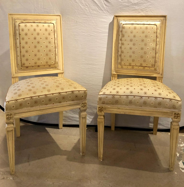 Set of Twelve Jansen style paint decorated and gilt Louis XVI style dining chairs. Each in a new upholstery with new springs and welts. The set with fine sleek and clean lines in a linen white form of parchment faux paint with gilt hi lights. The