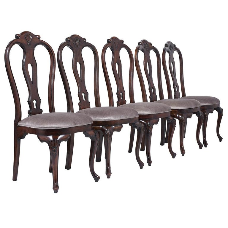 An extraordinary Vintage Set of Twelve Dining Chairs handcrafted out of solid mahogany wood and are stained a rich dark mahogany color a satin lacquered finish,. This fabulous set features two armchairs & ten side chairs with finely frame details