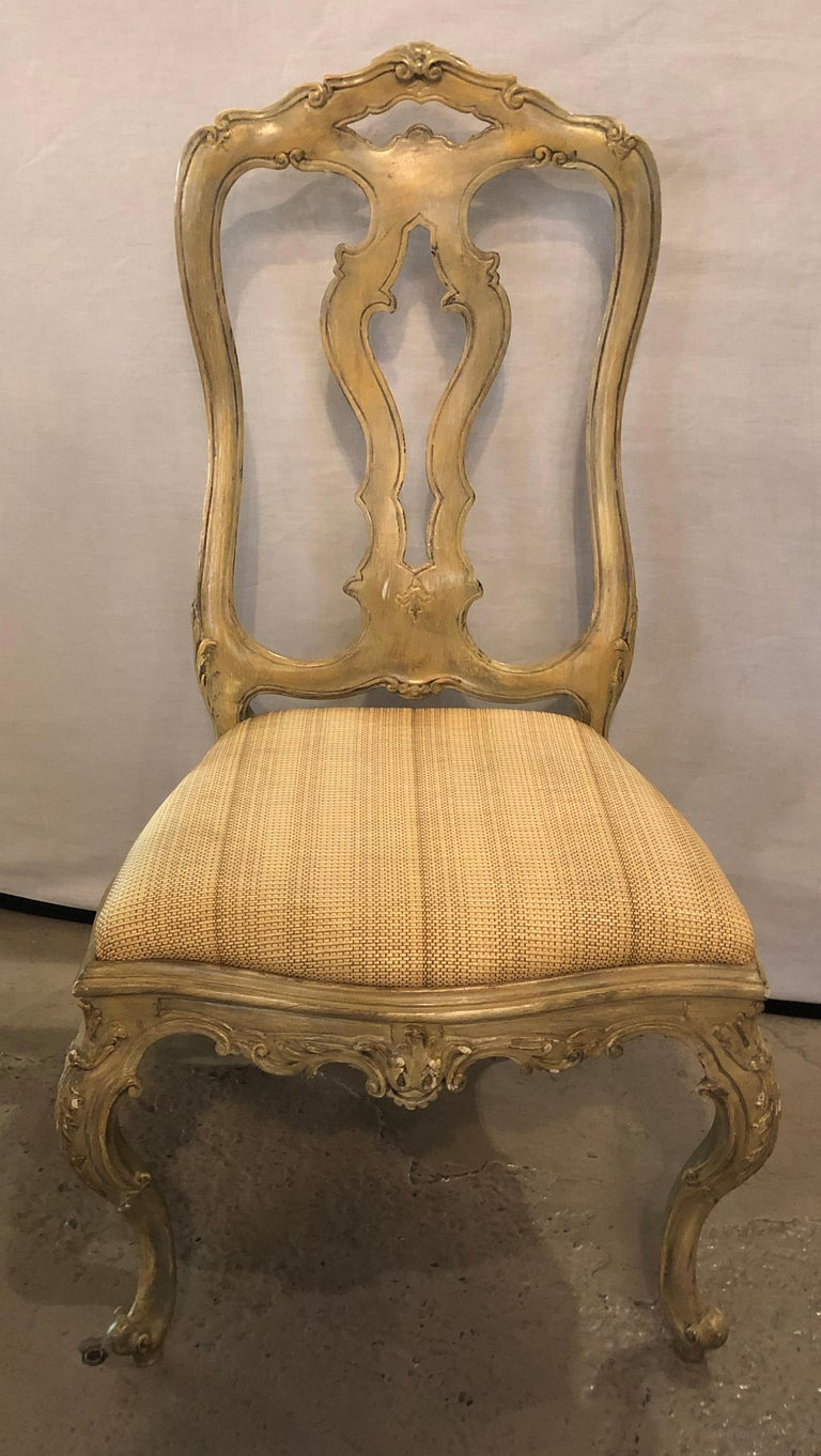 Set of twelve paint decorated Italian Rococo dining room chairs. This magnificent set of twelve (12) dining room chairs are wonderfully carved with arched backrests supported by a shell carved apron and cabriole legs. The whole in a very nice olive