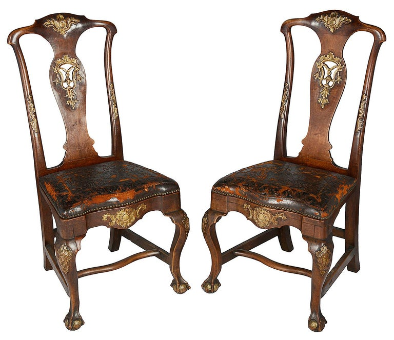 A very good quality set of twelve 18th century Portuguese dining chairs, each with carved and fretted gilded foliate decoration, stuff over embossed leather seats, raised on elegant cabriole legs, united by H stretchers.