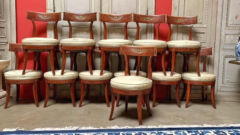 Twelve Regence style dining chairs with klismos style legs and a double headed eagled carved on each chair. They are not large chairs but are comfortable. The few of the chairs have had some old repairs and could be refinished or lacquered. They