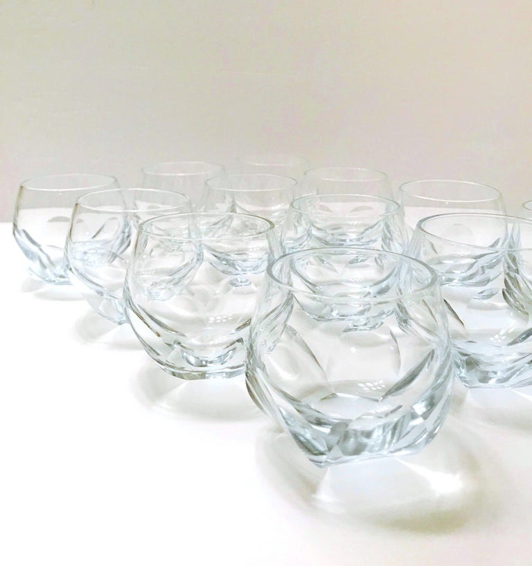Set of twelve vintage barware glasses with faceted design. The rock glasses have chic round bubble forms with handcut prism bases much like a glass honeycomb. Hand blown glass with a very subtle pale blue cast. Makes a handsome addition to any