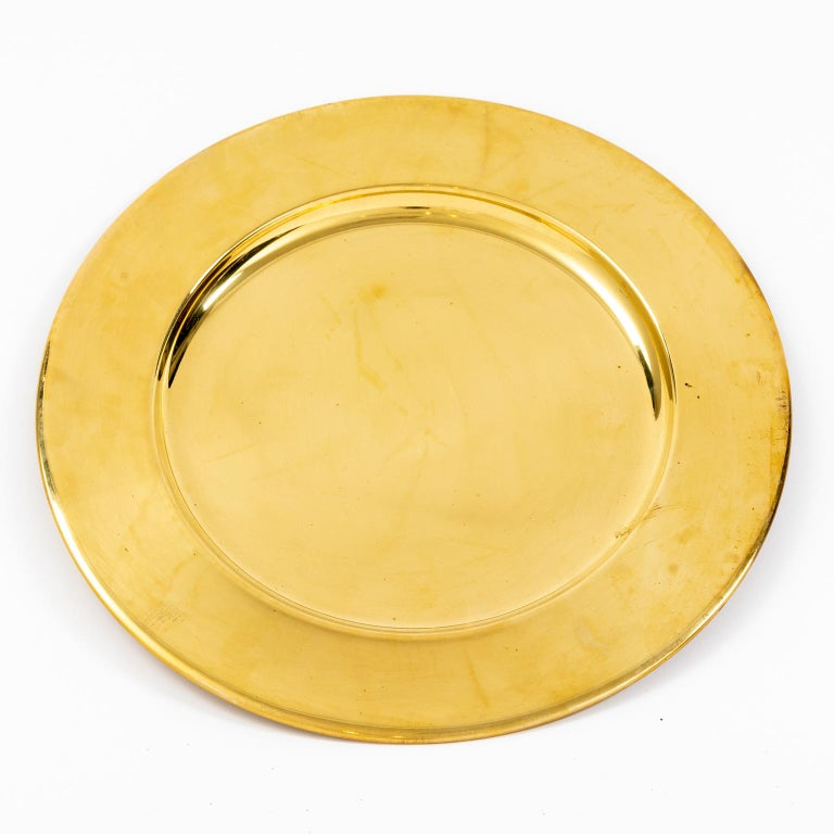 Set of twelve vintage 12.00 inch brass charger plates, circa mid-20th century. The brass is bright and shiny with light handling, these appear to have never been used. Please note of wear consistent with age including minor wear, slight scratches,