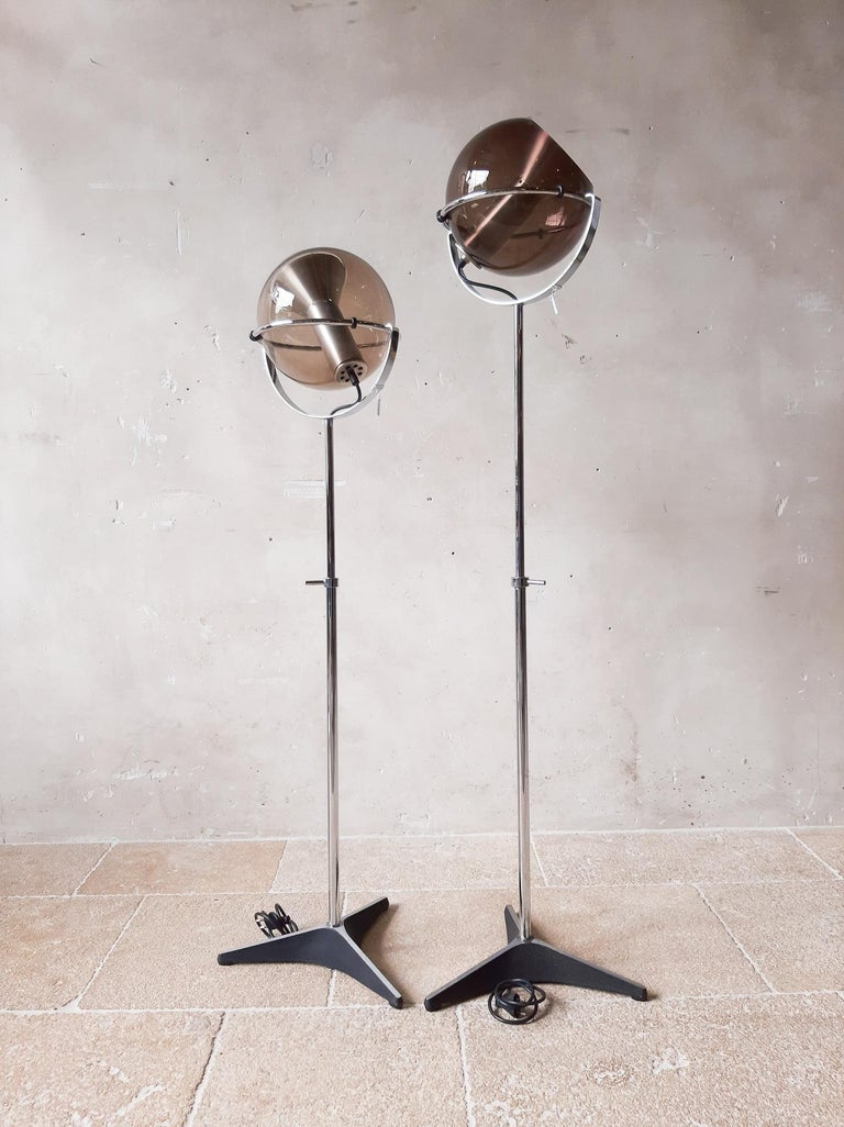 Dutch vintage design classic. The Globe floor lamp by Raak Amsterdam designed by Frank Ligtelijn in 1961. The ball is made of gray/ brown smoke tinted glass and lies in a height-adjustable chrome ring.  35 cm in diameter, maximum height of 125