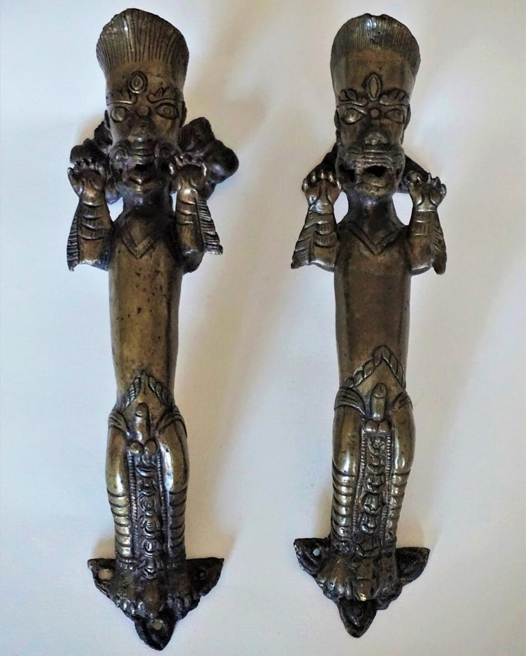 A rare set of two handcrafted heavy bronze door handles from an old temple in Nepal, mid-19th century. Figurative male sculptures depicting a fertiliy deity used on entry doors as a symbol to ensure fertility by touching. Please also look closely at