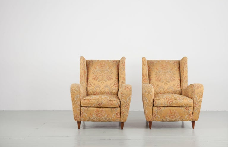 Set of two armchairs designed by Melchiorre Bega. These elegantly proportioned wingback chairs feature tapered walnut legs and are upholstered in their original fabric in a golden colour and with ornamentals.  Feel free to contact us for more