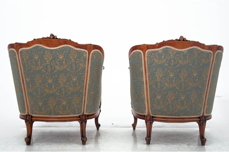 A set of two armchairs and table, France, circa 1920.  Very good condition. After professional renovation and replacement of the upholstery with a new one.  Wood: walnut  Dimensions:  Armchairs height 88 cm, seat height 50 cm, width 76 cm,