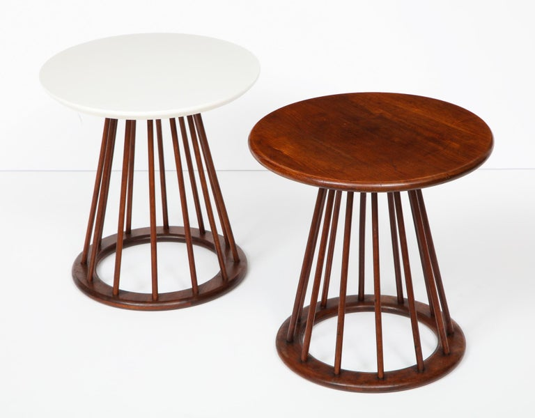 Set of two round spindle leg side tables designed by Arthur Umanoff and produced by Washington Woodcraft, circa 1950's. One table has a walnut top and walnut base; the other has a walnut base with a white micarta top and white painted edges. Both