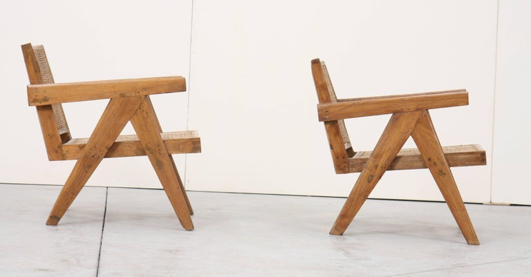 In teak with profiled and slightly curved backrests and bent seat. Detected and profiled armrests and side compass design legs. Cane seat and backrests.