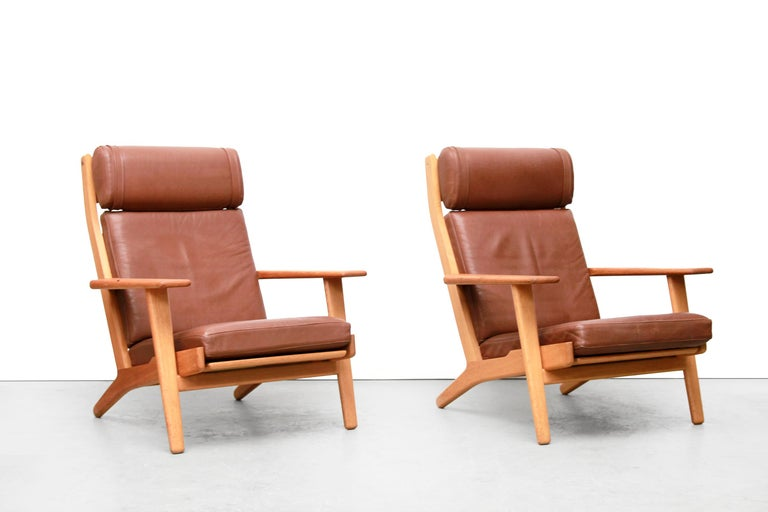 Two armchairs by Danish top designer Hans Wegner. Hans Jørgen Wegner was one of the most inventive of Danish furniture designers. These armchairs are made of solid oak and are originally covered in brown leather. What is very important in Denmark is