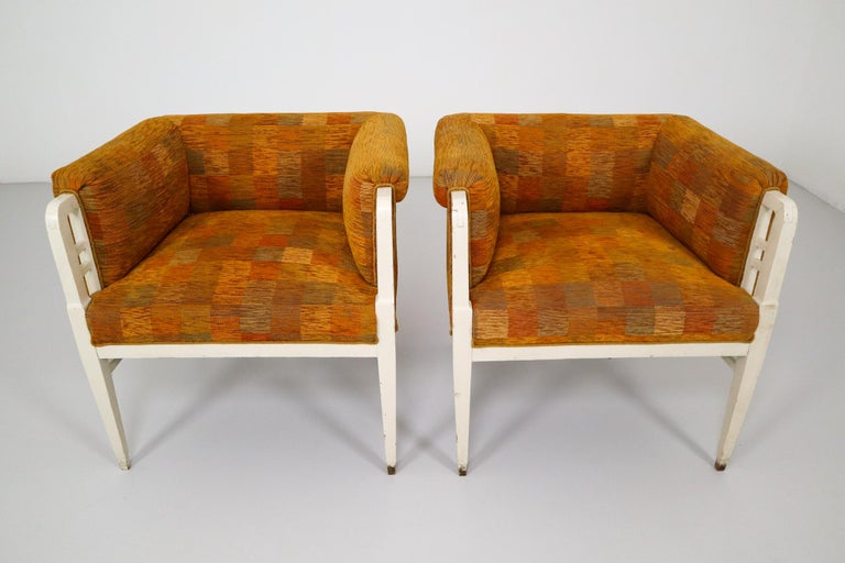This is a set of two armchairs in the style of Jugenstil. It's made of white painted wood and an orange fabric. The upholstery can be replaced, ask us for more information about the possibilities we can offer.