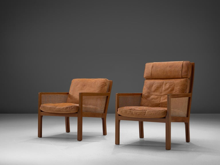 Bernt Petersen for Wørts Møbelsnedkeri, Adam & Eve lounge chairs, in mahogany, cane and leather, Denmark, 1964.   Set of his and hers armchairs in mahogany and cane, upholstered with loose cushions in patinated cognac leather. The design is quite