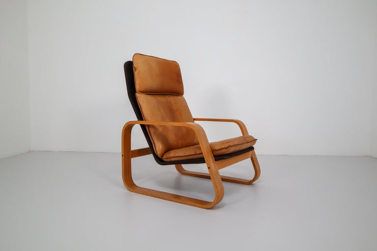 Set of two late midcentury lounge chairs, patinated leather, bentwood and fabric , France, 1970s.