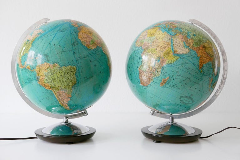 Set of two Mid-Century Modern duo earth globes or side table lamps. Manufactured by Columbus Verlag, Berlin and Stuttgart, 1960s, Germany. The globes are illuminated, and can be used as side table lamps.  Executed in glass, aluminium and wood. The