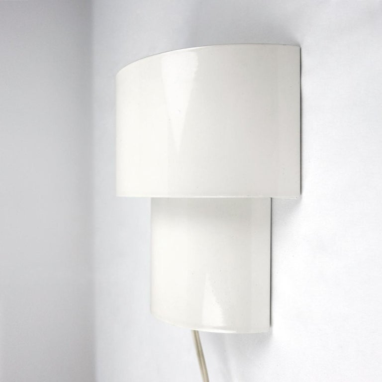 These glossy white steel sconces are composed by two different sized half circles that intertwine. The effect of this is that beautiful diffuse light shines on three places on the wall: above, half way and underneath the fixtures. The lamps are not