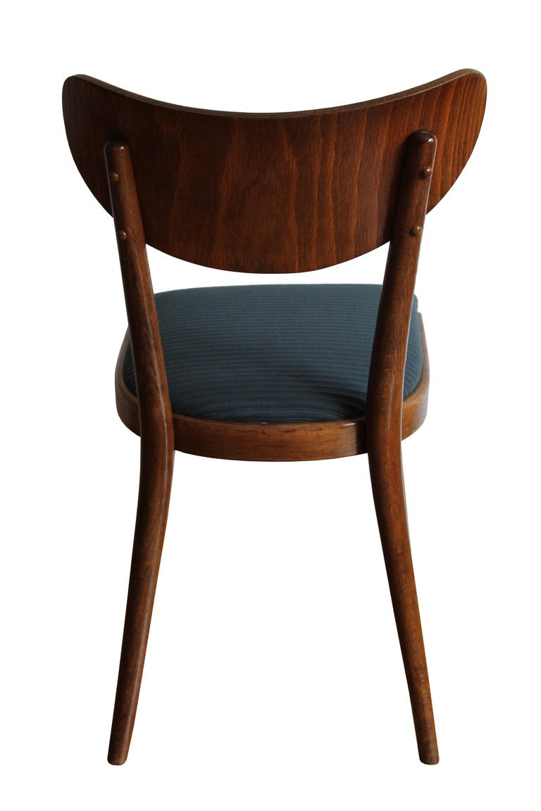 These elegant dining chairs were designed and produced by TON Company in Czechoslovakia. The shape of these chairs is based on the traditional Thonet/TON dining chair. The bentwood backrest however is a typical design aesthetic of the 1960s. The