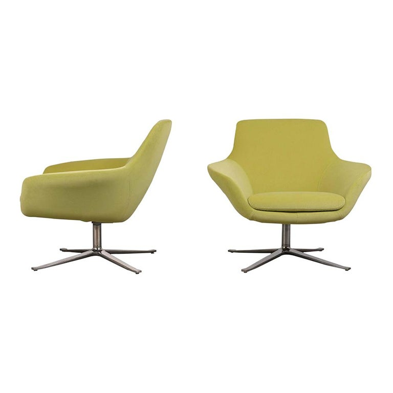 This restored set of 1980s lounge chairs are upholstered in light green velvet fabric and finished topstitch details. The chrome X-base allows the chairs to rotate with ease. This pair of swivel lounge chairs are sturdy, sleek, and ready to be used