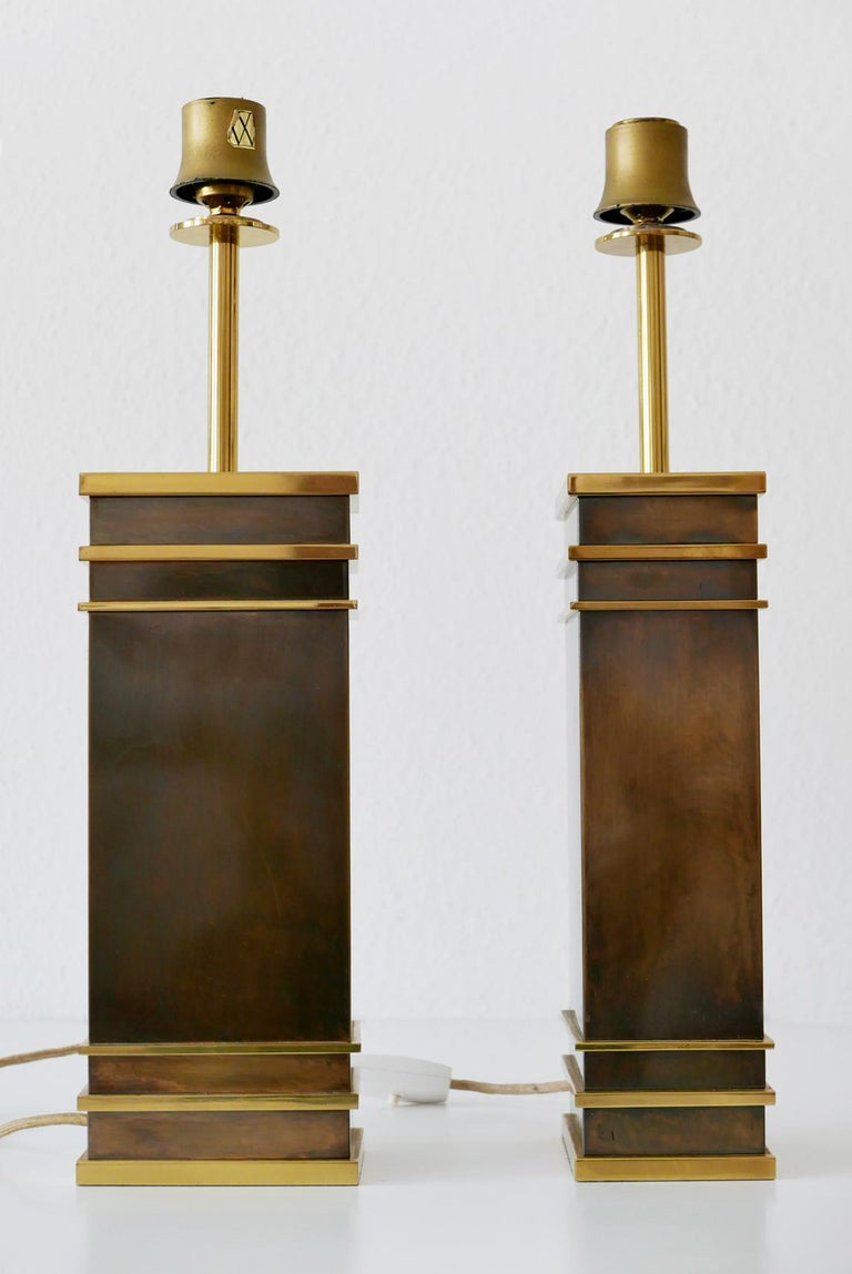 Set of two monumental and extremely rare Mid-Century Modern table lamps in heavy, massive brass. Designed and manufactured by Vereinigte Werkstätten, 1960s, Germany. One lamp with makers mark.  These sculptural table lamps are executed in massive