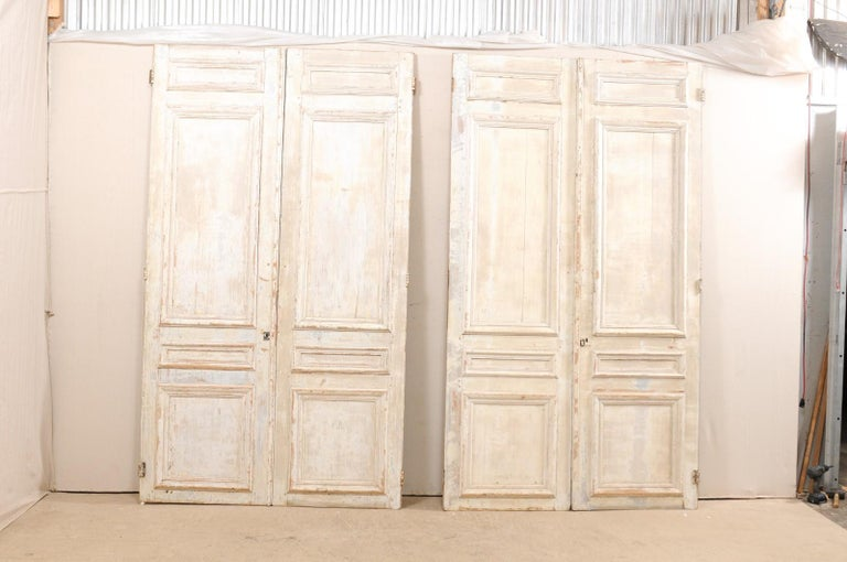 A set of two pairs of French panel doors from the mid-19th century. This set of 2 pair of French doors each feature four nicely molded panels at front, with more plain, recessed panels on their backsides, standing approximately 8.75 feet in height.