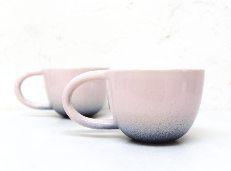 """Set of two wheel-thrown white stoneware mugs with a modern spray glazed pink and indigo glossy glaze exterior with a matte satin white finish interior.   Each mug approximately 6"""" x 4"""" x 3"""".  Carol Joo Lee is an artist who loves working with"""