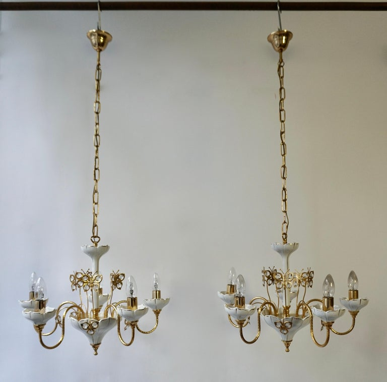 Two 1970s porcelain chandeliers with brass and crystal butterflies. Measures: Diameter 52 cm. Height fixture 40 cm. Total height including the chain and canopy 110 cm. Five E14 bulbs.