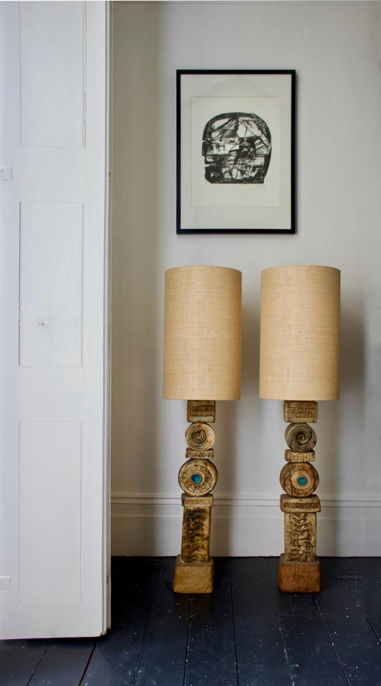 A set of two heavy ceramic TOTEM lamps by Bernard Rooke, England, 1960s.  Sculptural statement pieces, made up of ceramic elements in natural tones of terracotta and stone. The two are of the same broad design but each lamp is unique, due to the