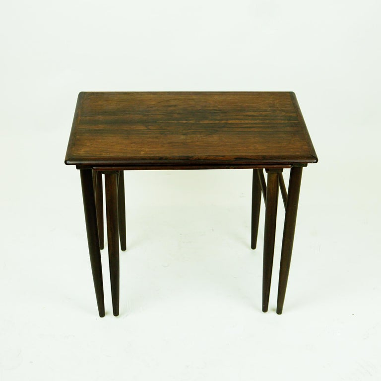 This set of two rosewood nesting tables was designed by Poul Hundevad for Fabian Denmark in the 1960s. The tables are made from finest rosewood and are in very good slightly restored condition. Beautiful tapered legs the small table slides into the