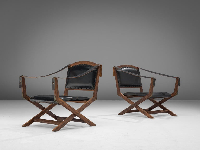 Set of two armchairs, in rosewood and leather, Scandinavia, 1940s.   Two foldable safari chairs in Indian rosewood and black leather upholstery. These X-chairs have a classical appearance with several references to ancient furniture. These