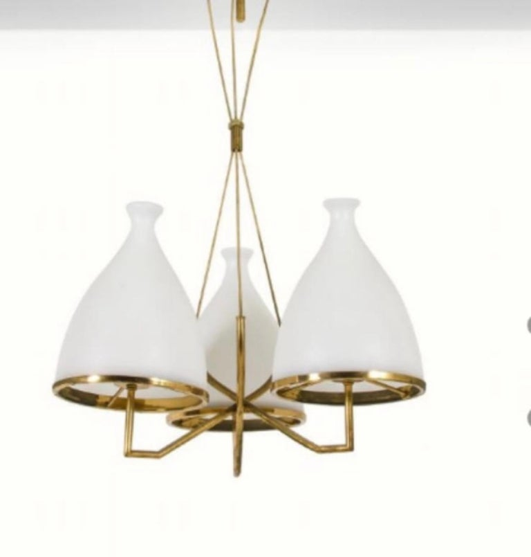 Two amazing chandelier made in Italy by Stilnovo in the 1950s, the structure in polished brass it's in original patina and the white satin glass diffusers are in excellent conditions. They works 110-240 volts, each chandelier needs three regular e27
