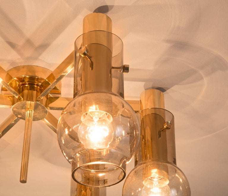 Chandelier, smoked glass, brass, Sweden, 1960s.  Brass chandelier in the manner of Hans-Agne Jakobsson. The pendant contains six horizontal facing arms with one glass globe on each end. The chandelier is made from a very solid and high quality. The