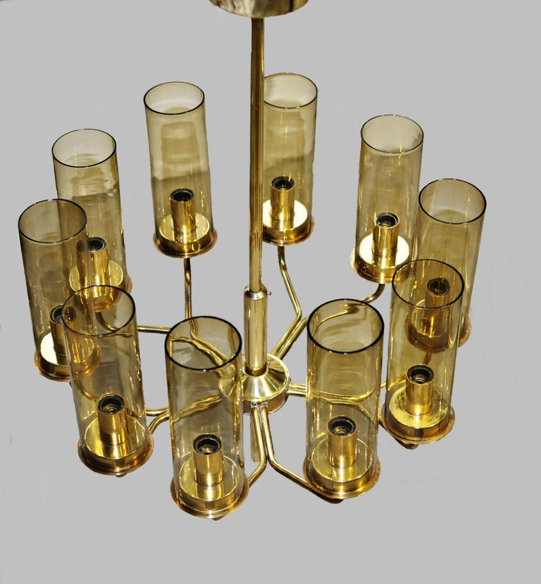 Set of two T10 chandeliers of brass with cylinder shaped shades of smoked glass, designed by Hans-Agne Jakobsson for AB in Markaryd, Sweden in the late 1960s-early 1970s.  The chandeliers are fully operational and in very good vintage