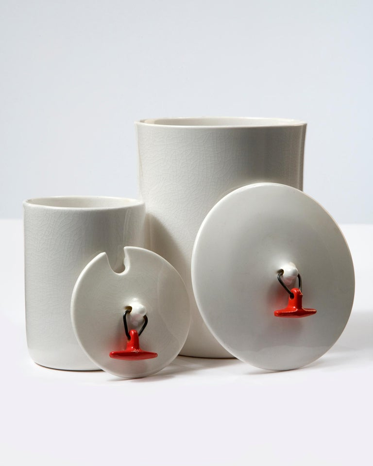 Set of two white ceramic canisters with red toggle-handled lids. Designed by La Gardo Tackett for Schmid International, Japan, 1950s.