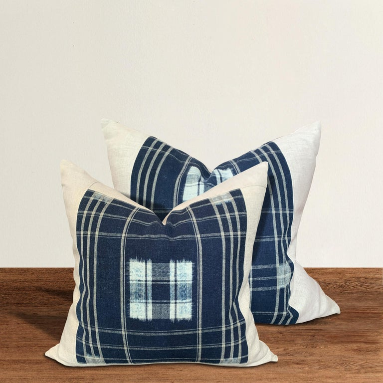 A set of pillows made from vintage Japanese handwoven blue and white indigo with a plaid pattern, filled with down. These pillows are slightly different sizes and slightly different patterns, making them a near pair.  Large: 21 in. W x 20 in.