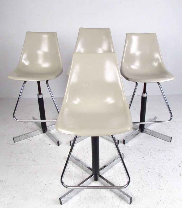 Set of four swivel stools by Krueger Metal Products feature sturdy mid-century construction and adjustable seat height. Substantial fiberglass seats set on chrome finish metal bases, ranging from 22 to 28 inch seat height the set is a versatile