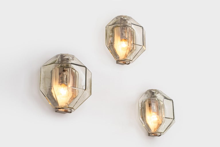 Rare set of three wall sconces by Vinicio Vianello for Vistosi, Italy, 1957. Wonderful polygonal shaped blown elements out of clear champagne colored glass. The glass elements are clamped between architectonic nickeled brackets which can be hanged
