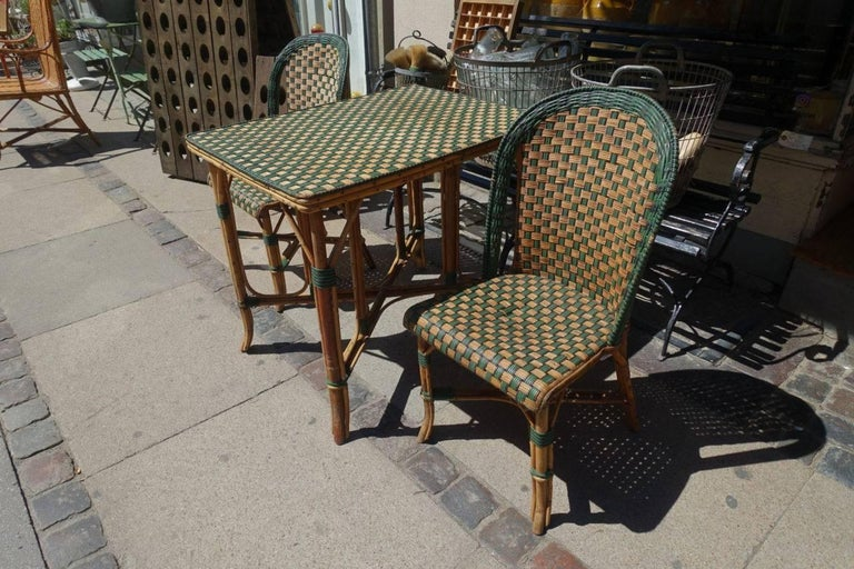 Ambiant vintage French furniture set, consisting of a table and two chairs. Handmade in rattan wickwork, in true bistro style. Lovely patina, and with a green and black striped pattern woven in.