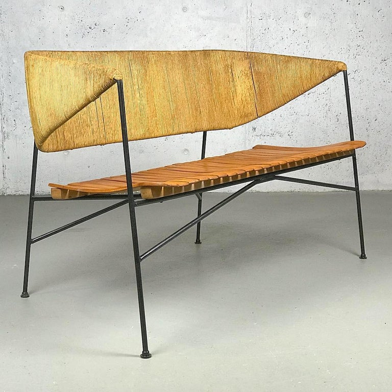 An exceptional museum-quality example of American Modern design from the 1950s - beautiful Minimalist settee designed by Arthur Umanoff for Shaver Howard and distributed by Raymor, in iron, wood and papercord. Patina/slight uneven color of