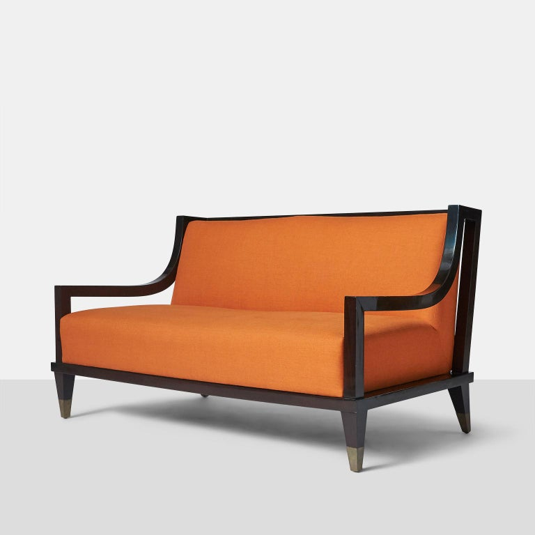 Settee by Mito Block Brothers A signature style settee by the Mito Block Brothers in Mexico City made in ebonized mahogany and square form brass caps on each leg. The back features a horizontal ladder back design with the upholstery being a